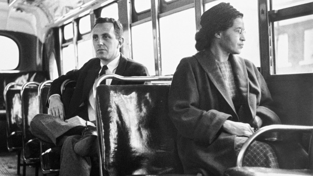 Rosa Parks sits in the front of a bus in Montgomery, Alabama, after the Supreme Court ruled segregation illegal on the city bus system on December 21st, 1956. Parks was arrested on December 1, 1955 for refusing to give up her seat in the front of a bus in Montgomery set off a successful boycott of the city busses. Man sitting behind Parks is Nicholas C. Chriss, a reporter for United Press International out of Atlanta.